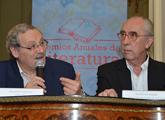 Se ve al ministro de Cultura y al director Nacional de cultura sentados hablando con el logo de los Premios Anuales de Literatura detrás
